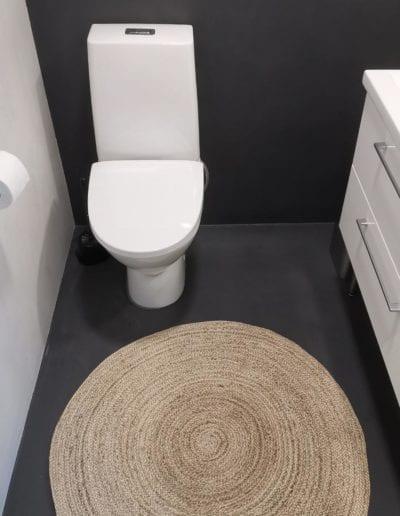 Mikrobetoni wc-tilan lattiaan. Värit tumma ja vaalea.